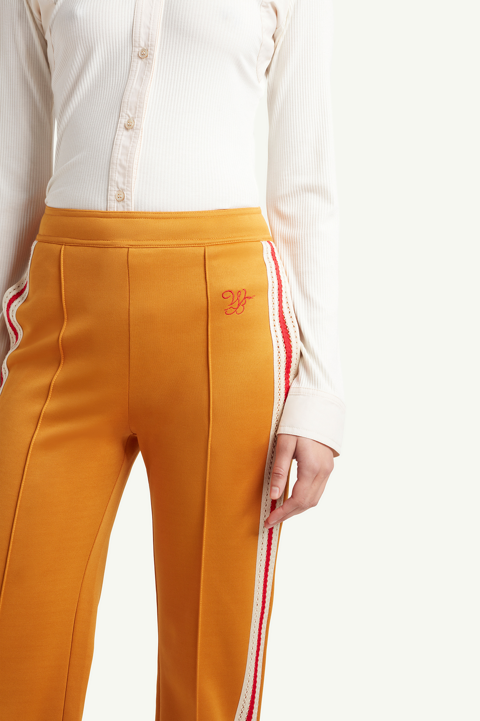detail shot of the mustard yellow Wales Bonner tracksuit trousers with red and blue line detailing and white long sleeve top