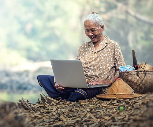 old woman smiling looking at computer