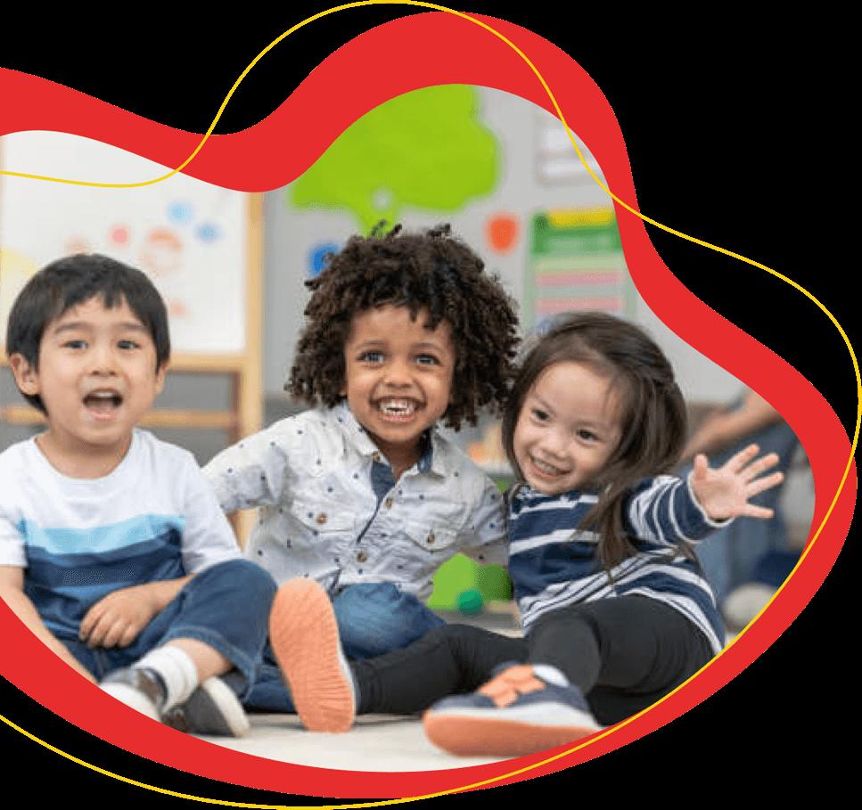 three preschool children sitting on the floor in a classroom smiling