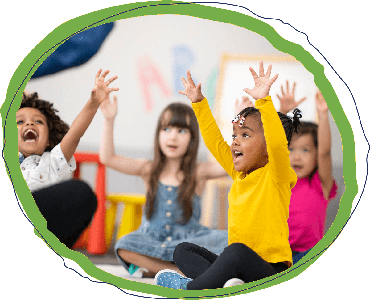 group of preschool children sitting in a classroom with their hands in the air
