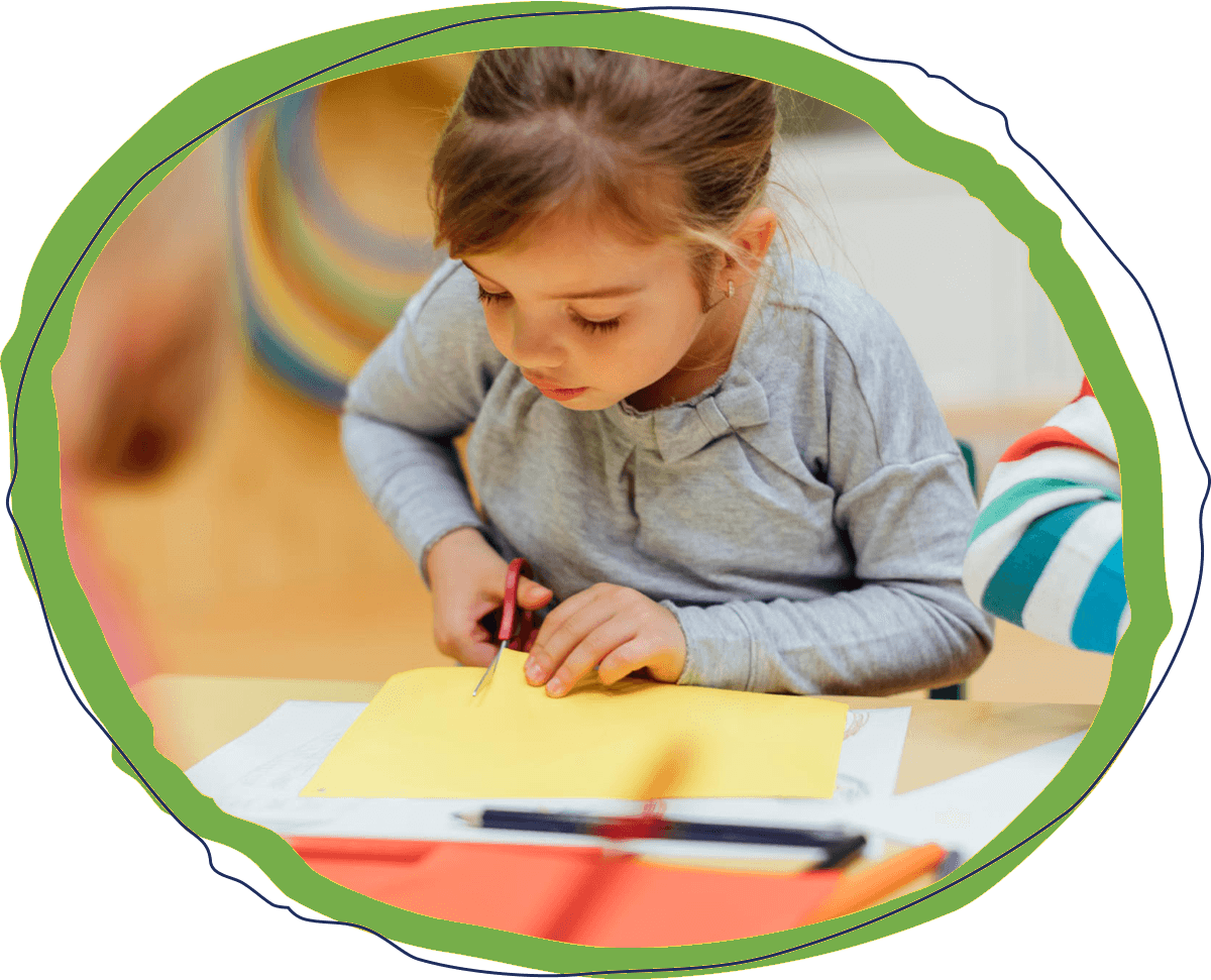 Little preschool age girl sitting at a desk cutting paper in a classroom