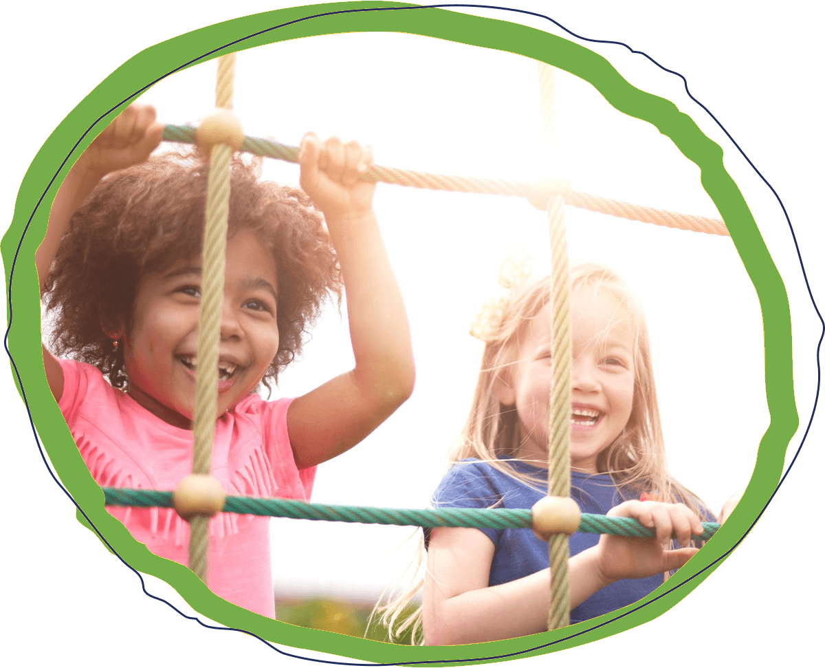 two young preschool girls smiling and climbing on a rope at a playground outside