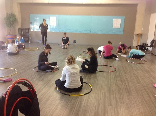 A group of people sitting on the floorDescription automatically generated with medium confidence