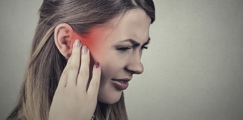 Woman suffering with ear infection pain