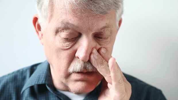 Man trying to breathe through his nose, suffering nasal blockage