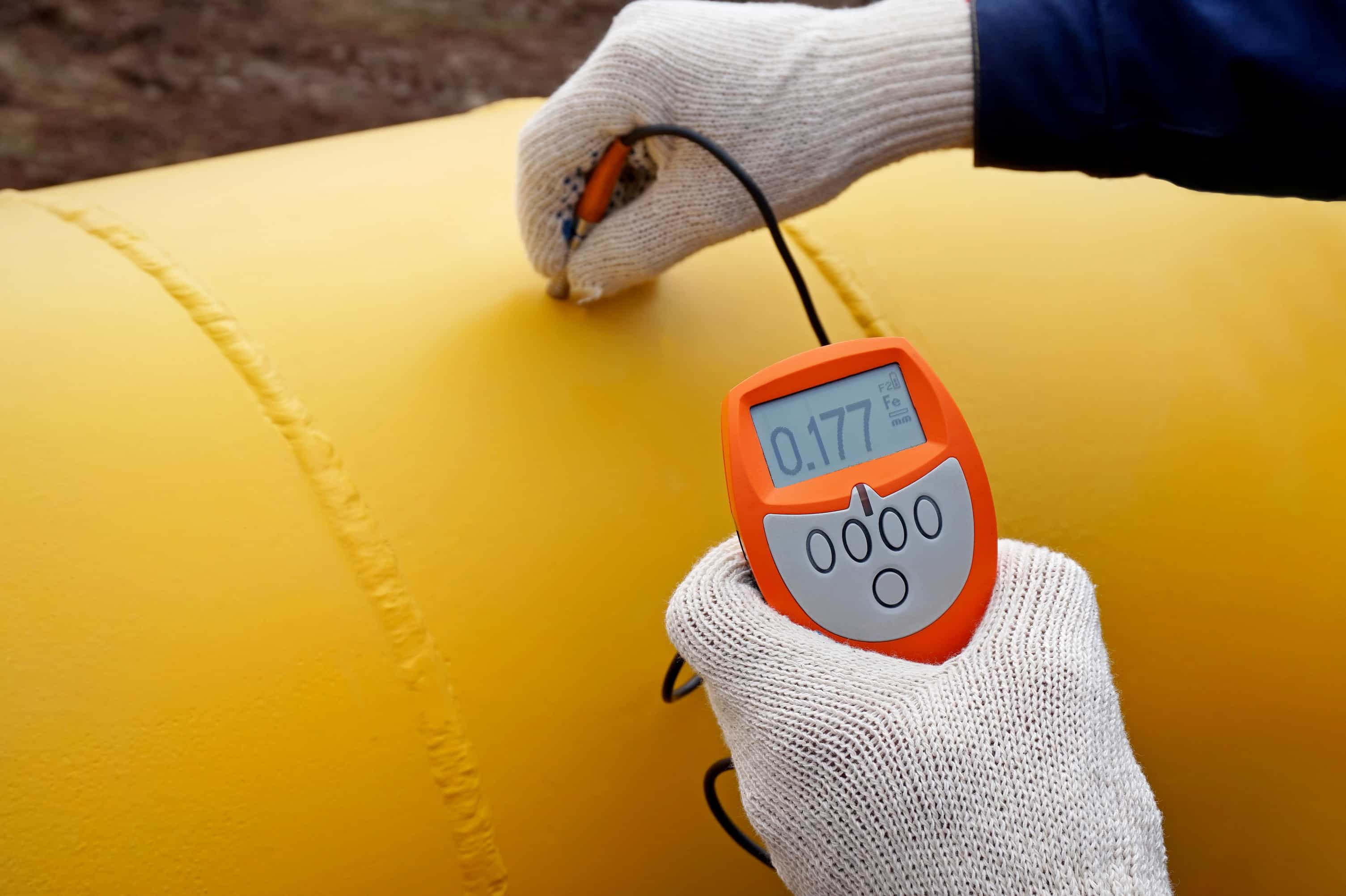Certified oil and gas crew member operating a coating gauge