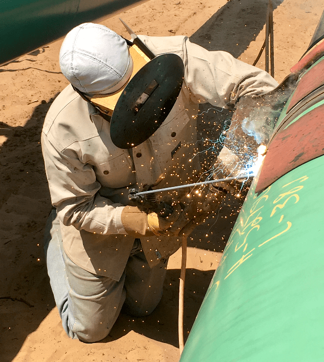 Sparks flowing as a certified oil and gas crew member welds a green pipe on a worksite