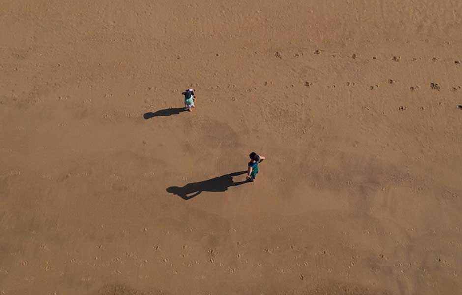 Two people standing together on sand