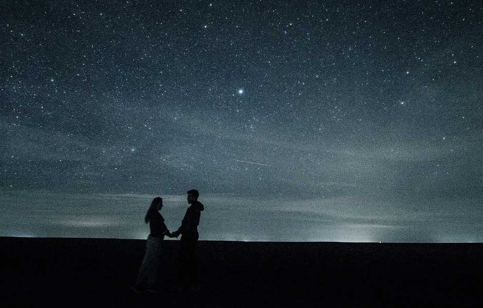 Couple holding hands under the stars