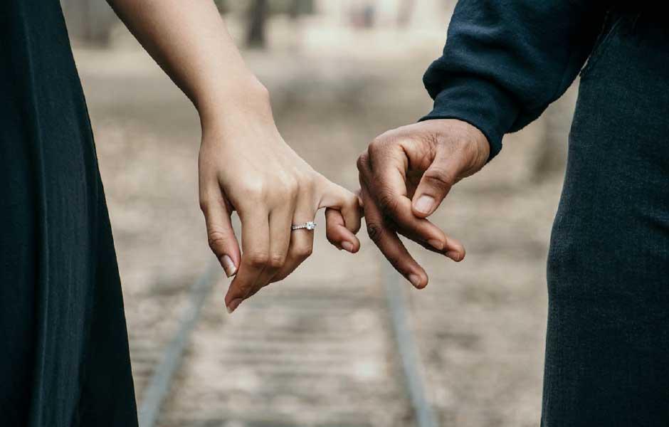 Couple interlinking fingers on a walk