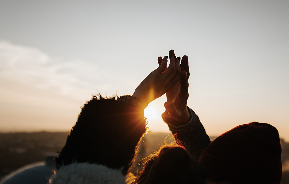 A couple touching hands in the sunset