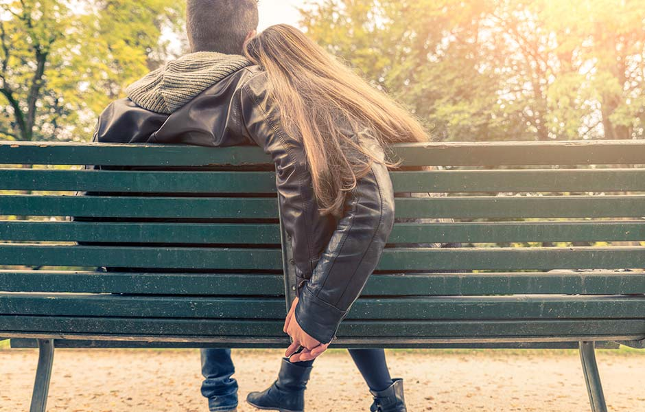 A couple sat on a park bench with the woman's head resting on her partner's shoulder