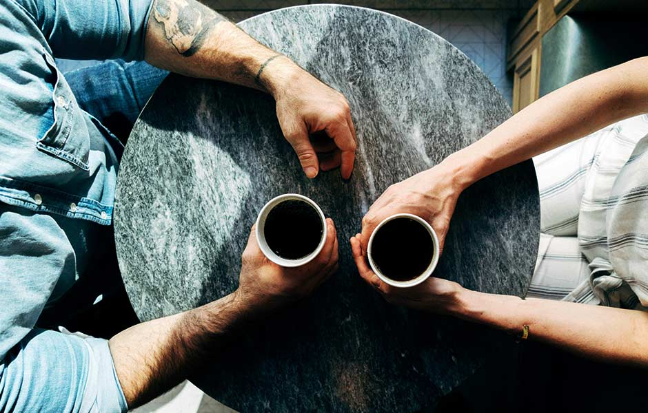 A couple sat at a marble table drinking coffee