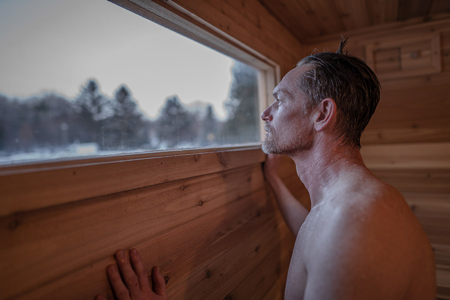 Man looking out of the window of a mobile sauna