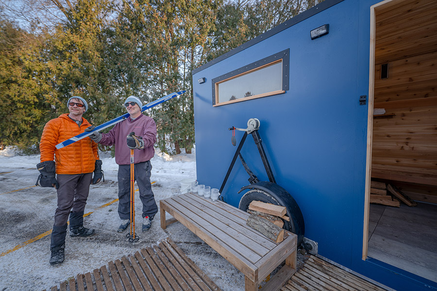 Two people standing outside of a mobile sauna