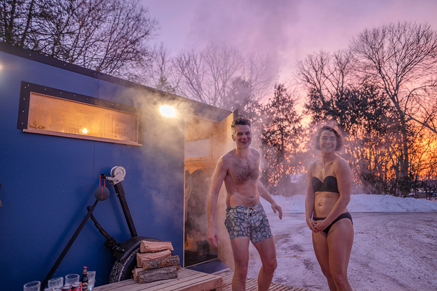Two people exiting a mobile sauna