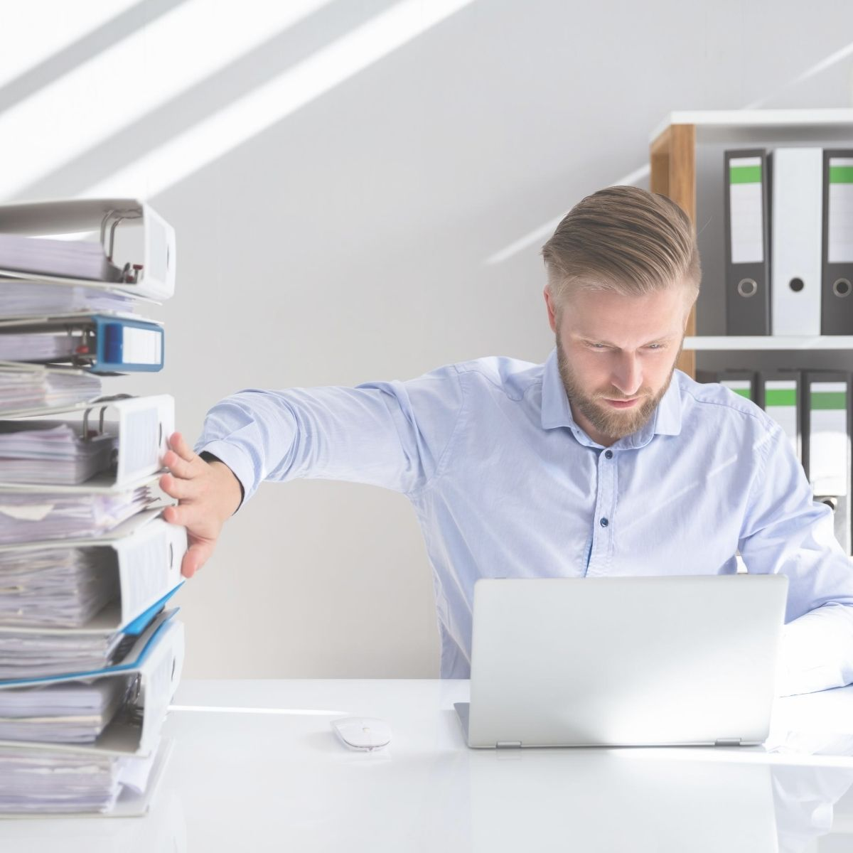 Man with a laptop and files stacked next to him