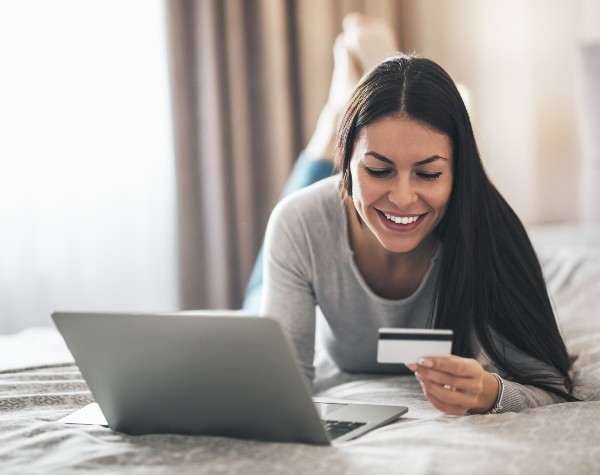 a woman on her computer using her credit card