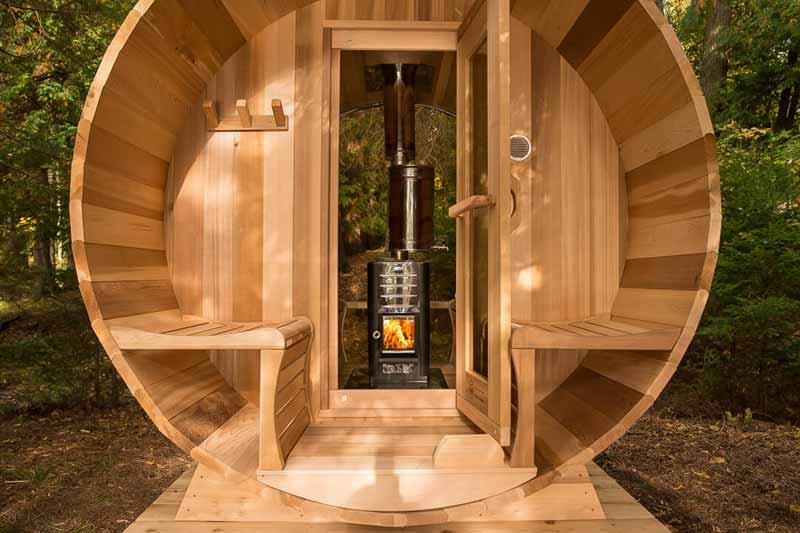 Eingang der Fasssauna – Tür geöffnet gewährt Blick auf Holzofen
