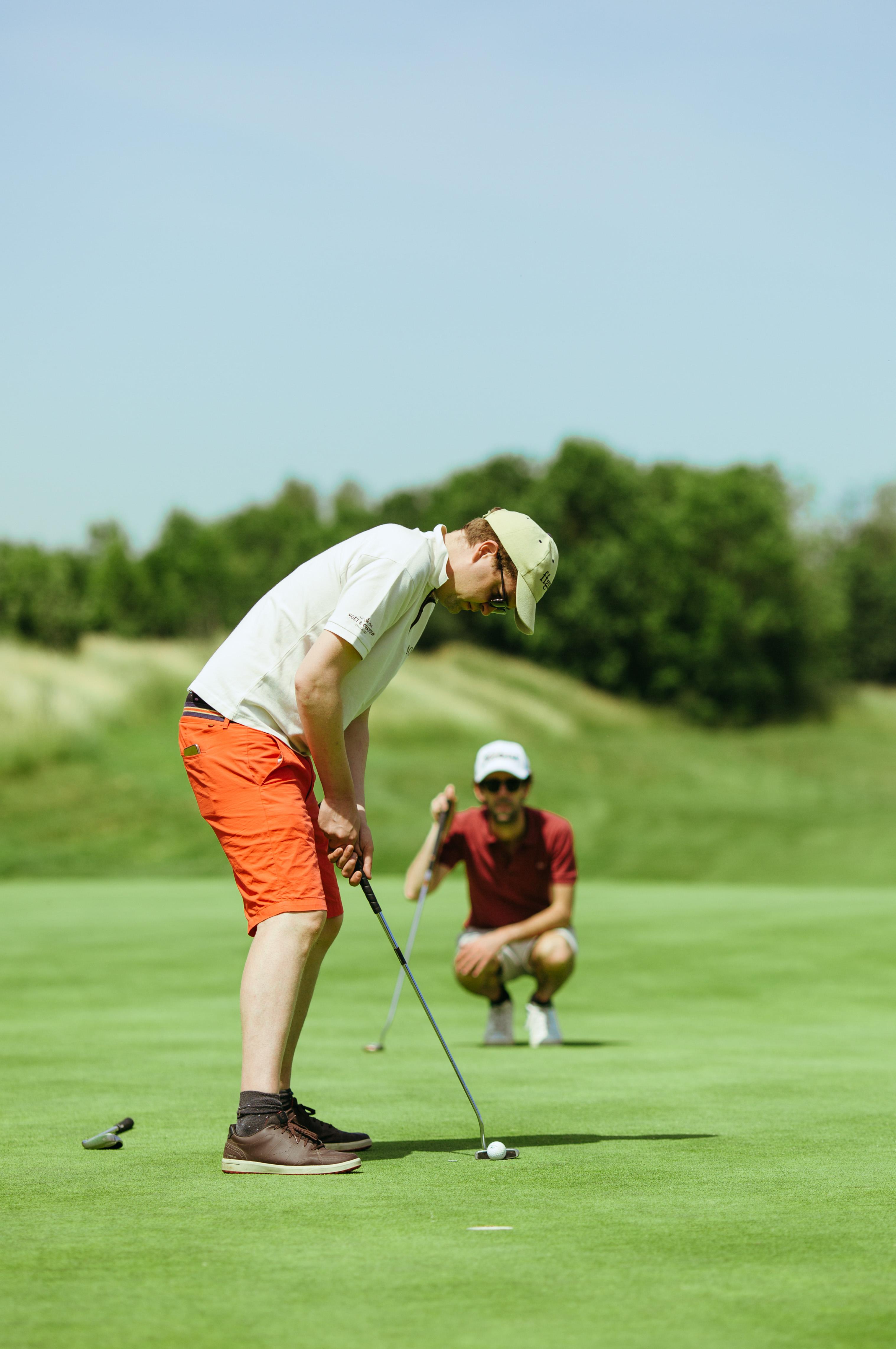 Golfeur à quelques mètres du trou ajustant son tir