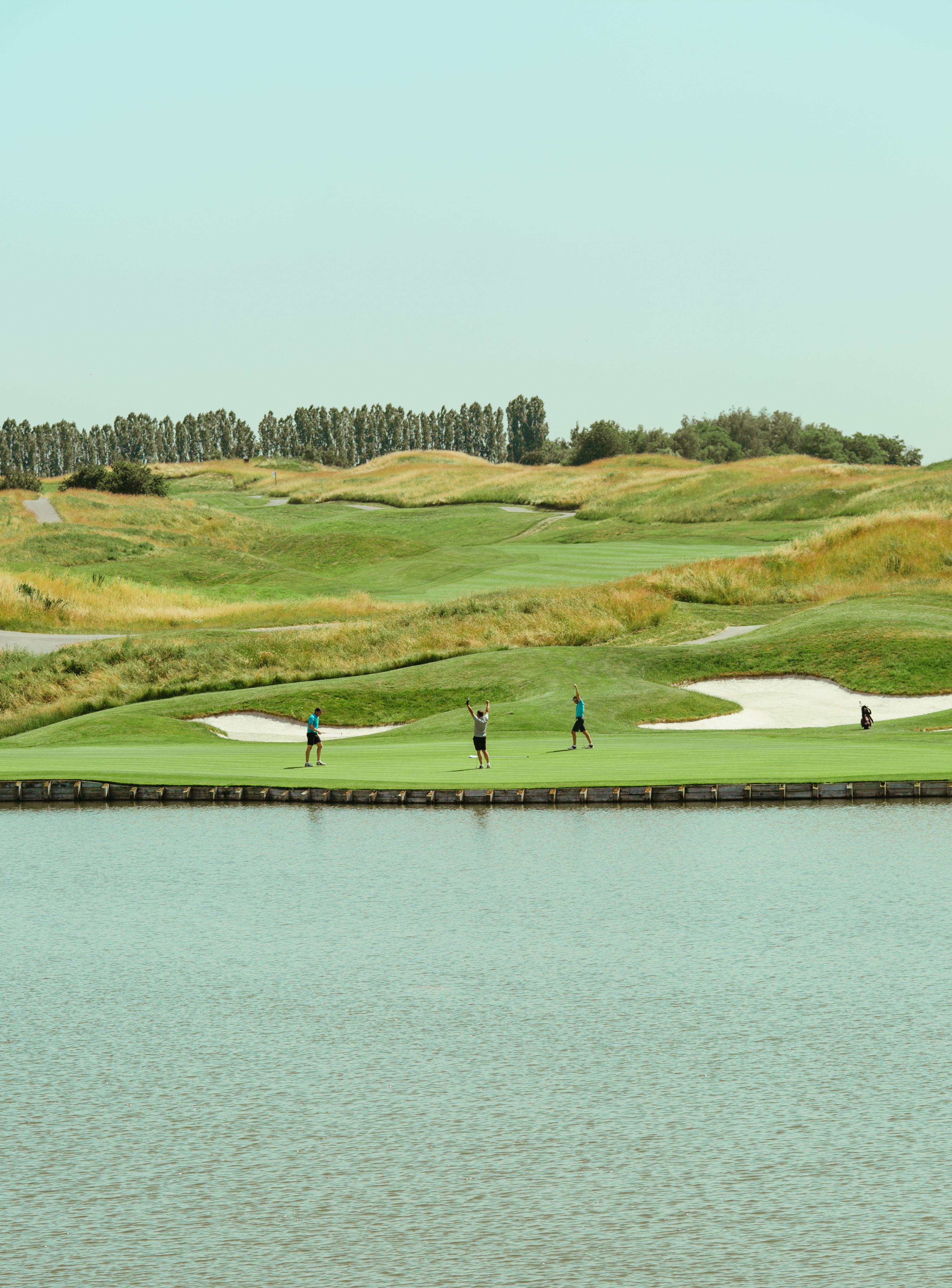 Golfeurs devant un étang ayant réussi un trou