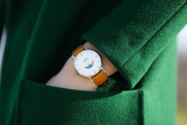 Montre valois bracelet en cuir gold portée par une femme au manteau vert