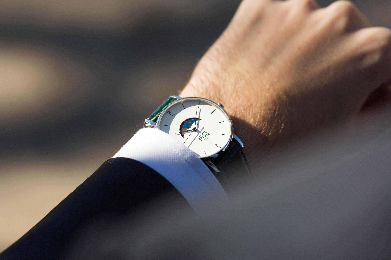 Montre Valois bracelet en cuir vert portée par un homme en costume