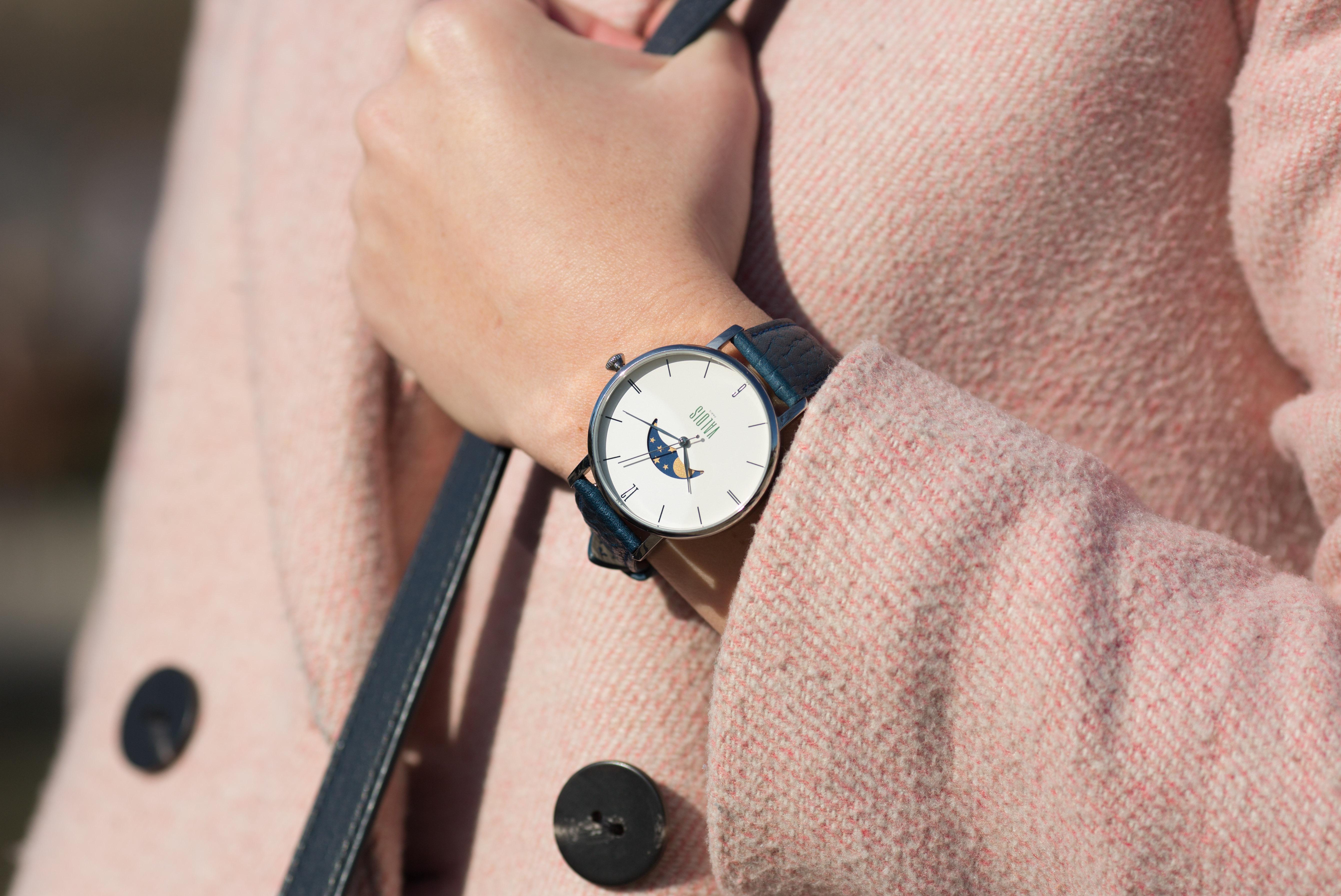 Montre Valois bracelet en cuir bleu portée par une femme au manteau rose