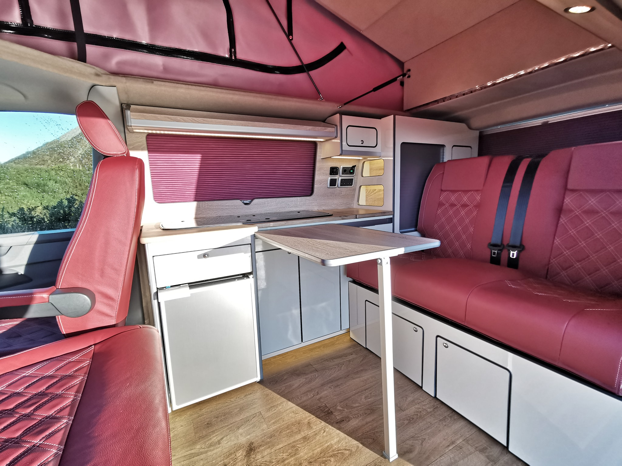 Red leather seats inside a campervan conversion