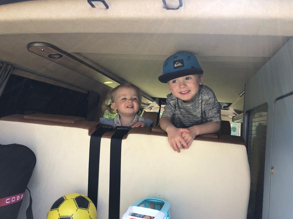 children leaning over the back of a campervan bed