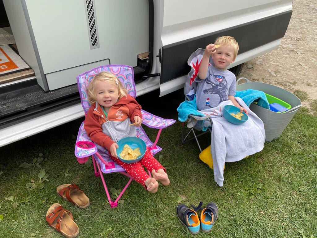 children sat in camping chairs