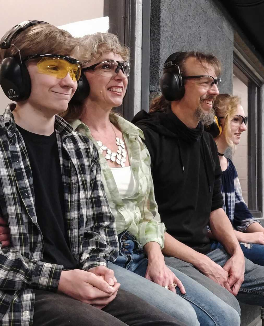 family-smiling-in-gun-range
