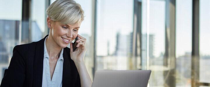 Telefonierende Frau vorm Laptop