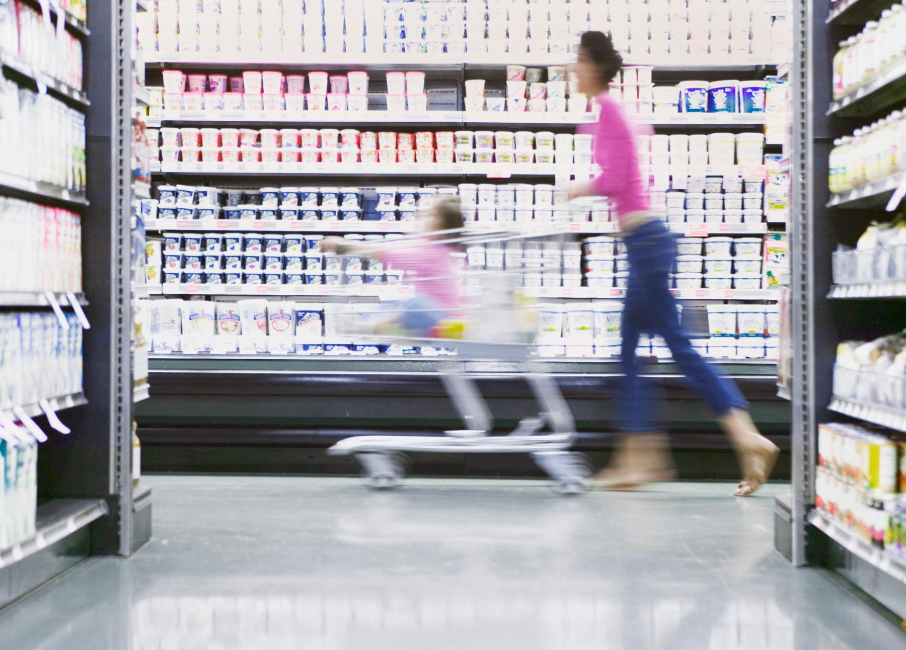 Hello retailer hero image showing a motion blur image of a woman pushing a shopping trolley around with a child.