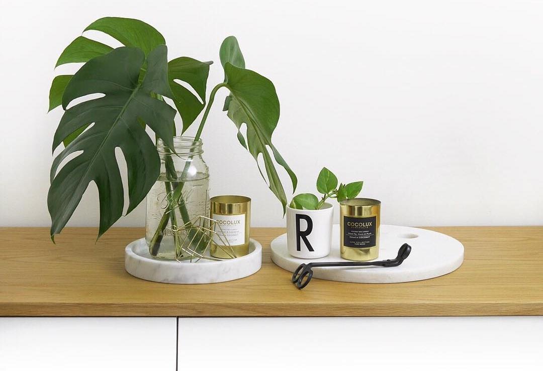 itens de decoração para casa de ouro e mármore com folhas de monstera e hera no fundo branco