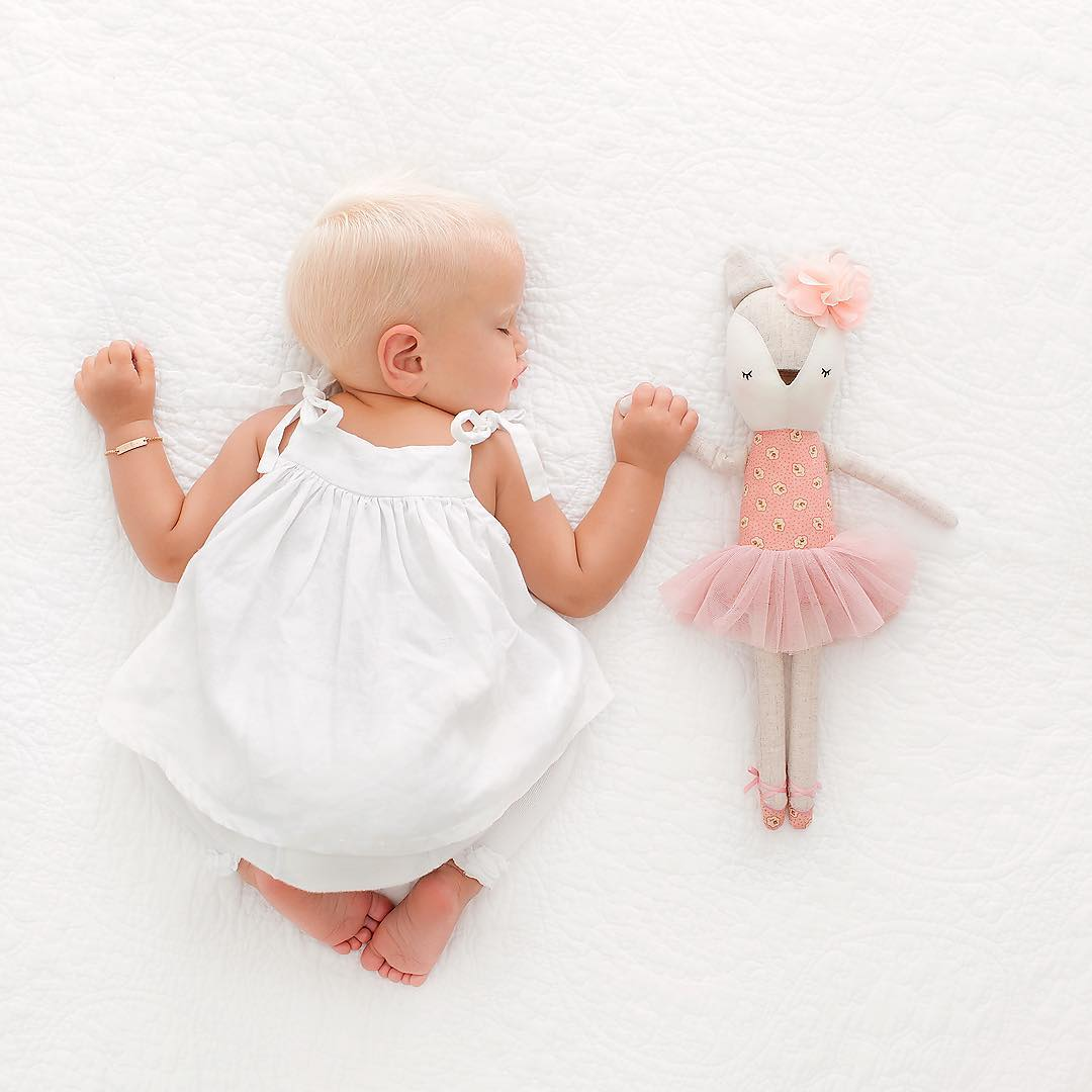 foto de menina na cama com boneca bailarina