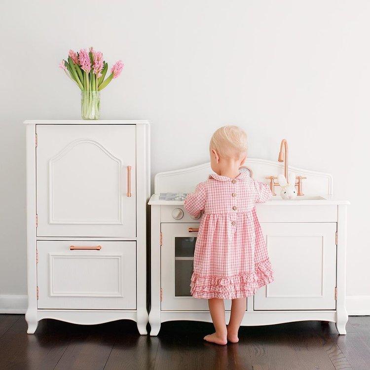 Foto de menina brincando na cozinha de brinquedo com alças de cobre e flores.