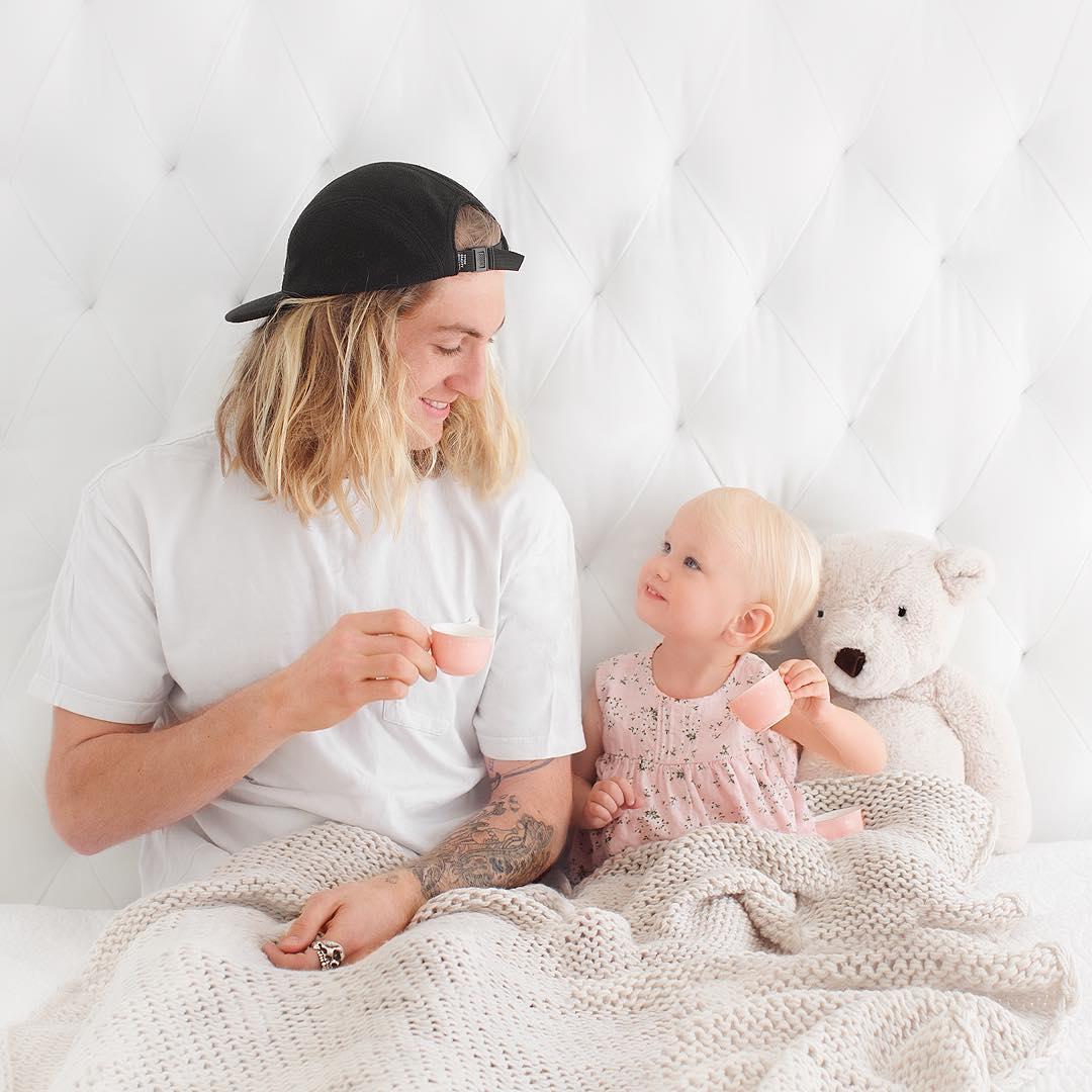 Foto de irmão mais velho tomando chá na cama com a irmã mais nova e bicho de pelúcia