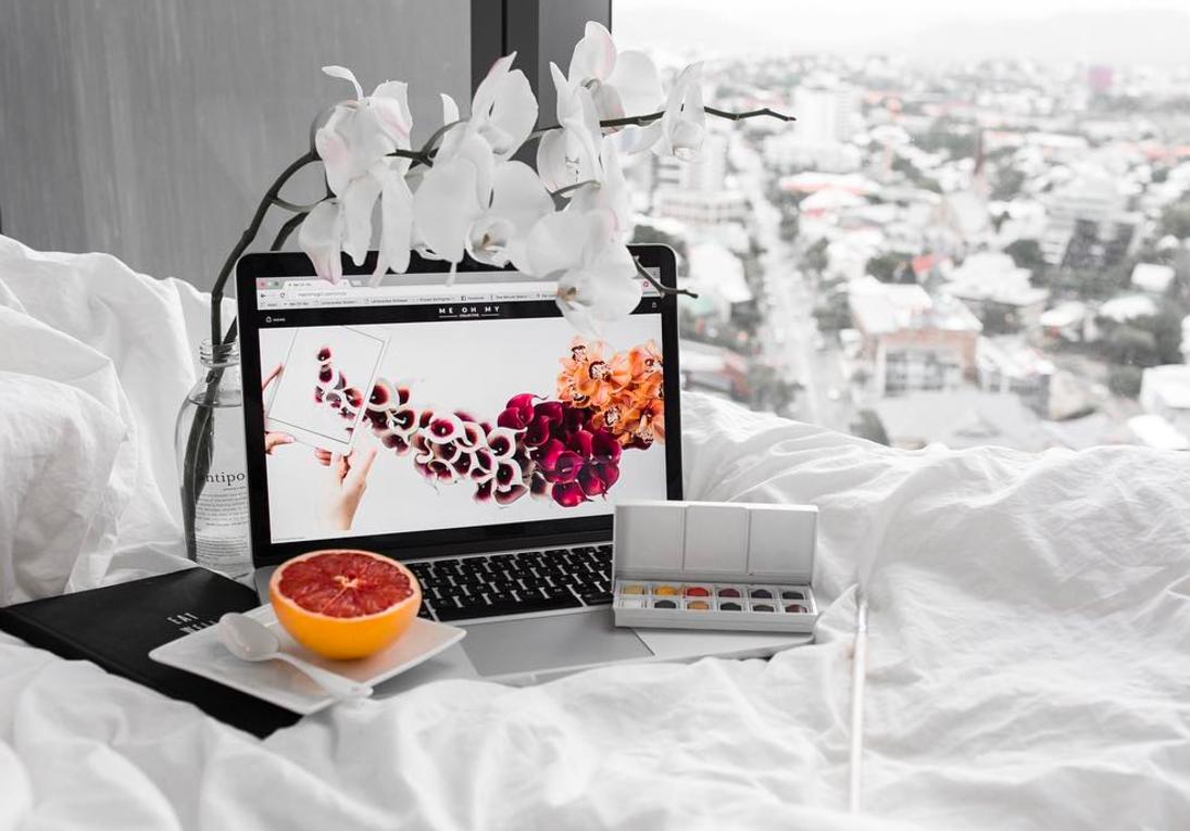 Laptop e paleta de tinta na cama com meia toranja
