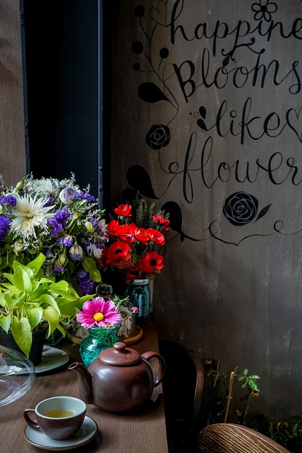 Vitrine da loja de flores e citação de felicidade na parede.