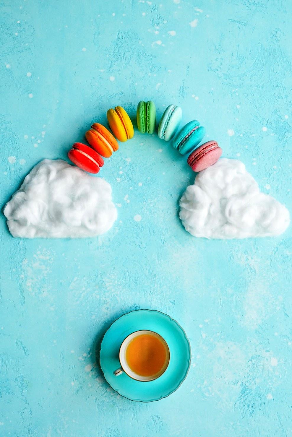 Flatlay alegre de um arco-íris feito de macarons e uma xícara de chá
