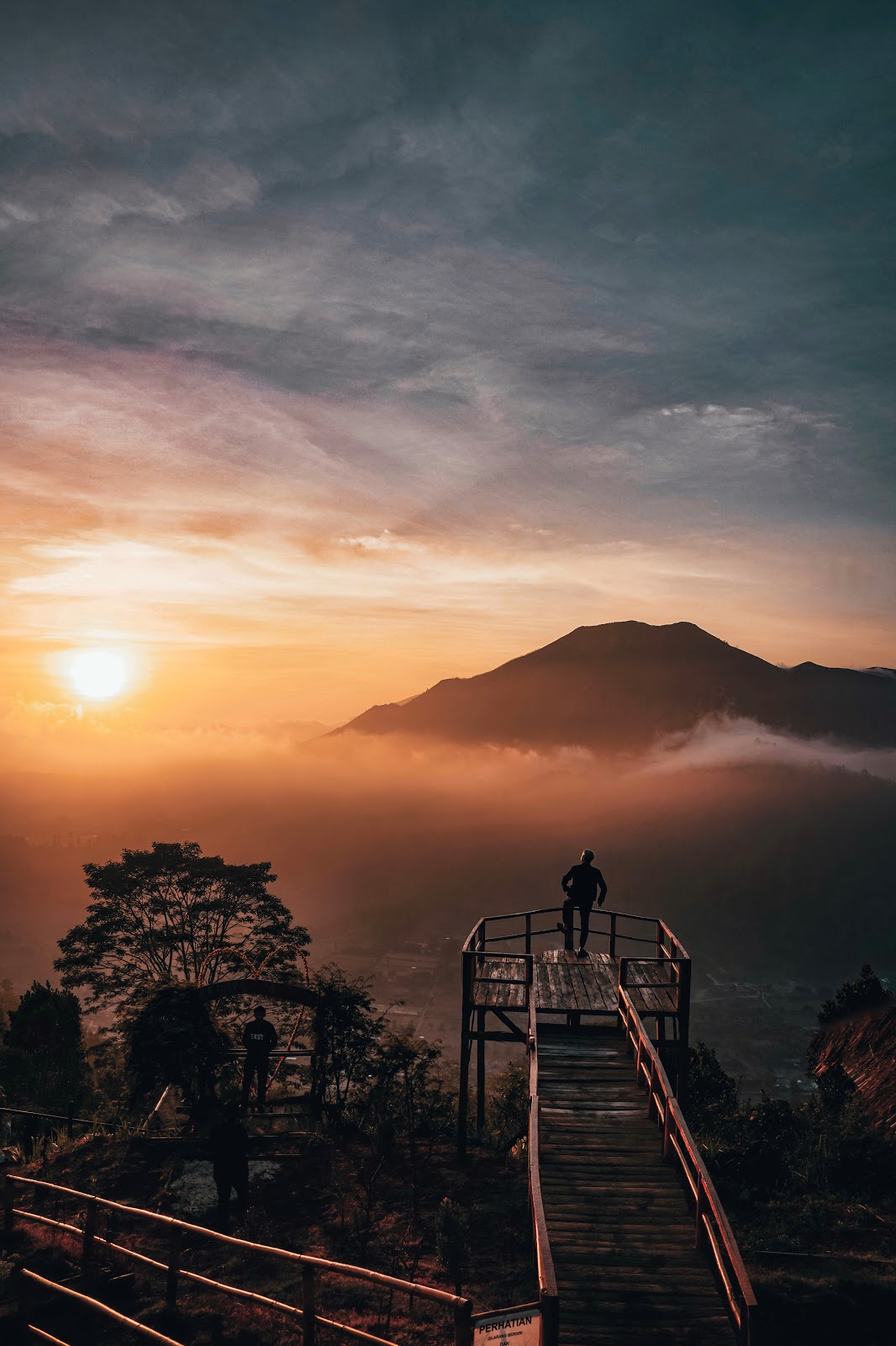 Foto do homem ao nascer do sol no miradouro do Monte Batur de Bali