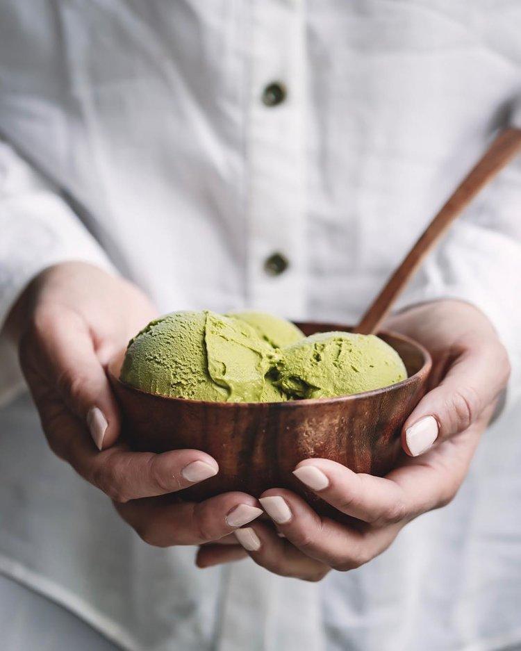 Mãos segurando um sorvete matcha em uma tigela de madeira rústica