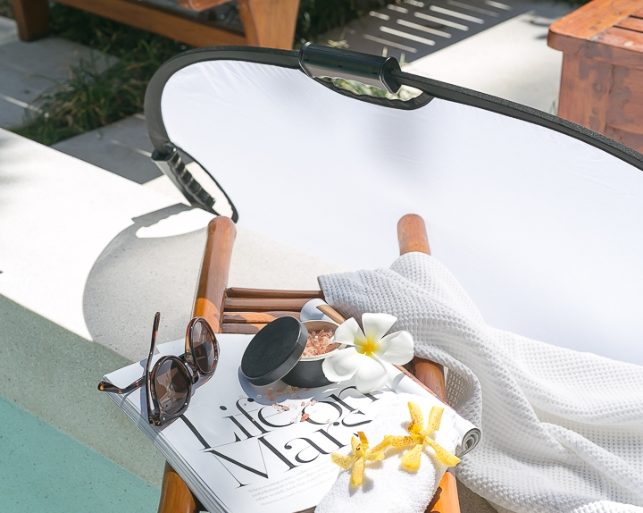 diffusing harsh shadows from poolside relaxing with magazine and sunglasses