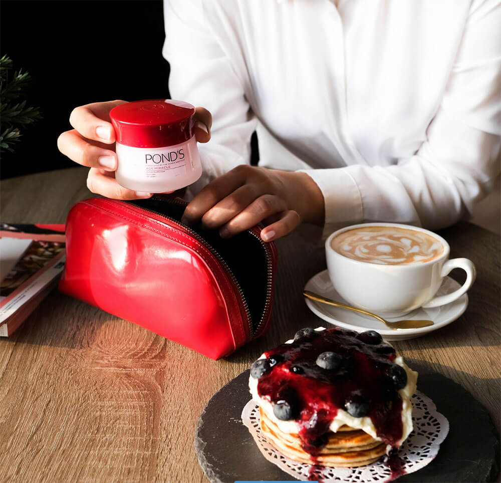 Produtos de beleza em estojo de maquiagem em cafeteria com café e panquecas