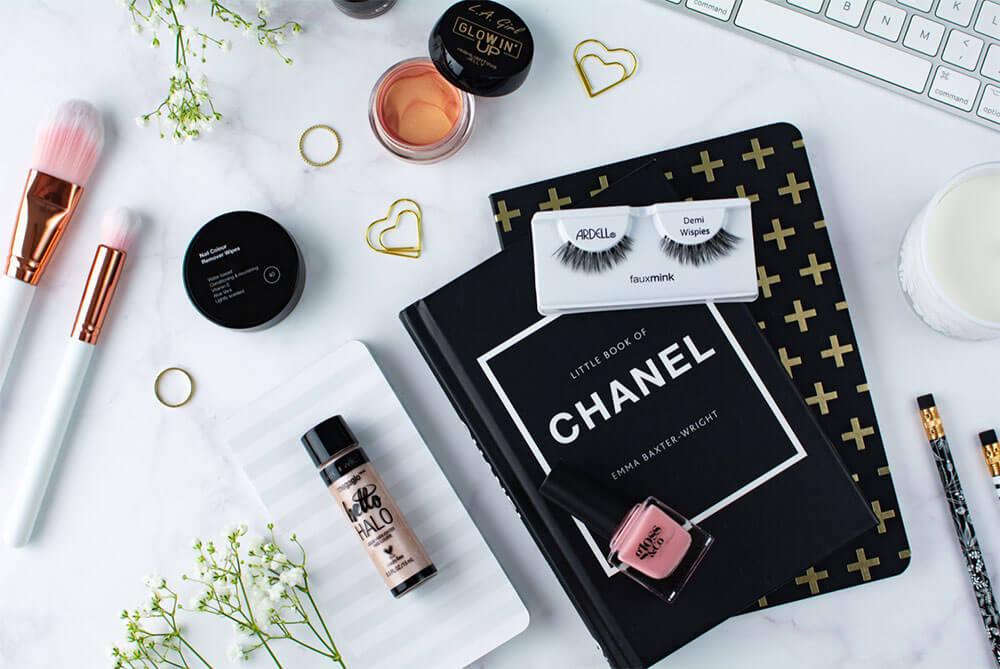 produtos de beleza e maquiagem em espaço de trabalho com papelaria e teclado de computador