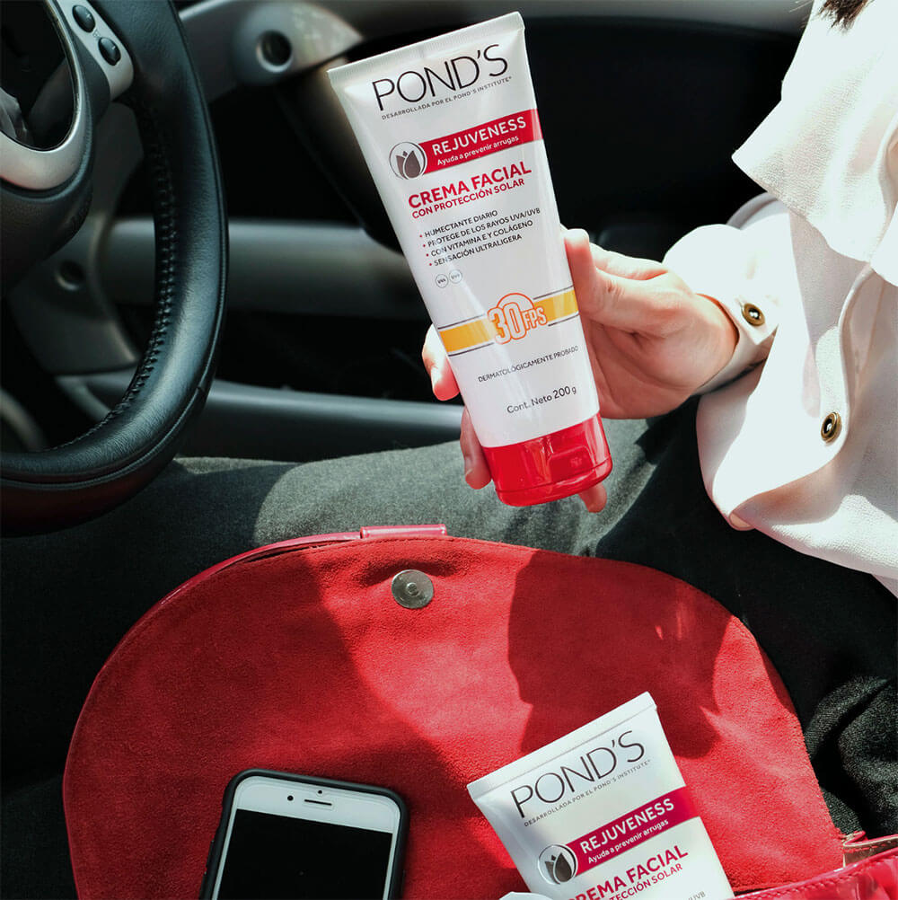 aplicando protetor solar de sua bolsa enquanto dirige um carro