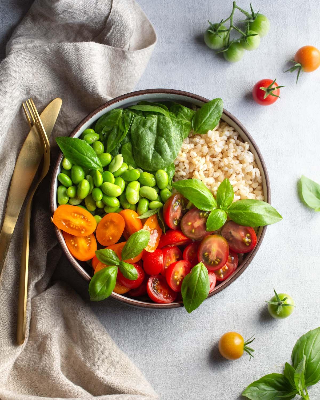 tigela nutritiva com arroz integral, edamame, manjericão e tomate fresco