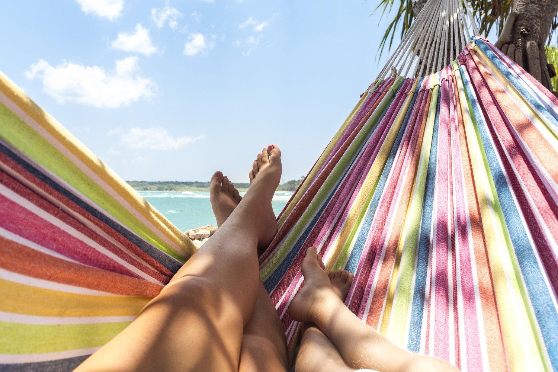 Pernas estendidas em uma rede listrada na praia ao sol