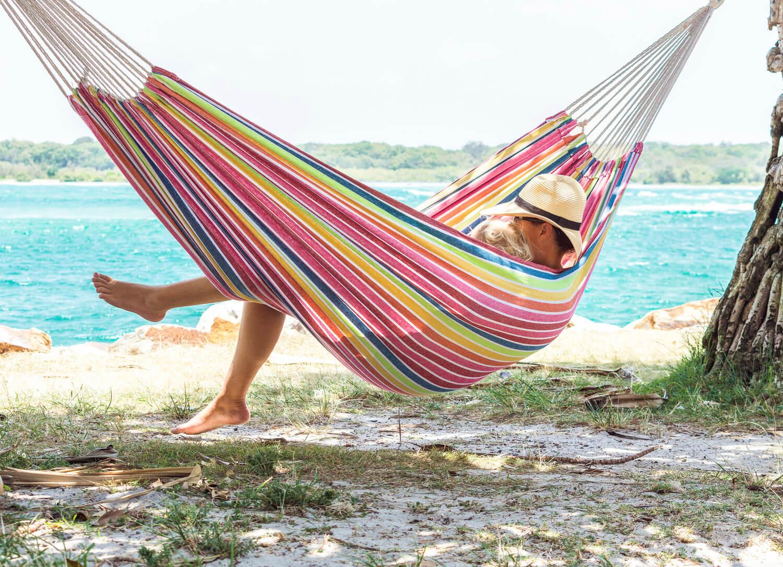 Ao ar livre na praia em uma rede listrada sob o sol salpicado de sol